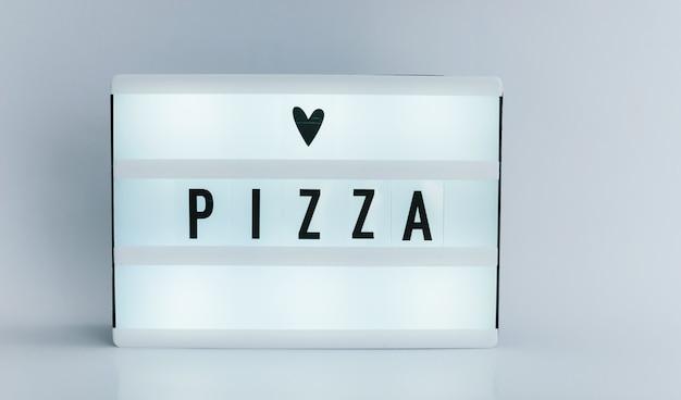 Leuchtkasten mit text, pizza an weißer wand