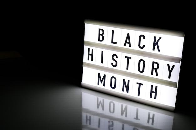 Leuchtkasten mit text schwarzer geschichtsmonat auf dunkelschwarzem tisch mit reflexion. nachricht historisches ereignis.