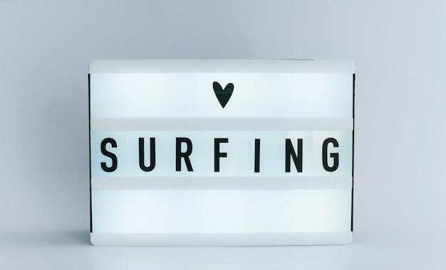 Leuchtkasten mit text, surfen an weißer wand