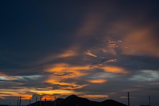 Leuchtorange- und goldfarben des sonnenunterganghimmels. sommerhimmel mit wolken während des sonnenuntergangs, landschaft mit einer himmelansicht über den hügel