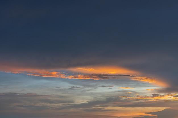 Leuchtorange- und goldfarben des sonnenunterganghimmels. sommerhimmel mit wolken während des sonnenuntergangs