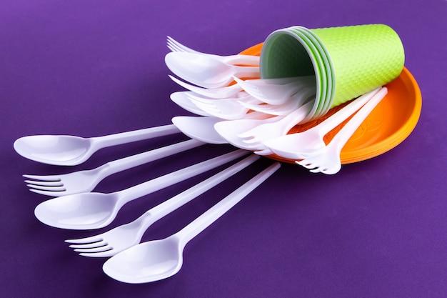 Leuchtorange- und grünsatz wegwerfplastikgeschirr auf purpur