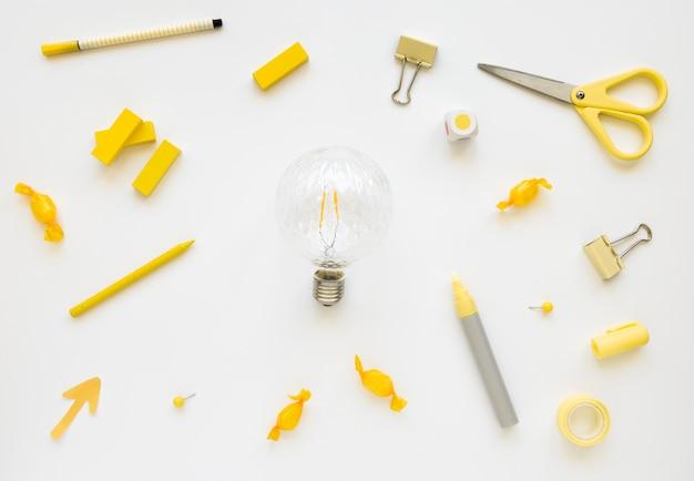 Leuchtstoffbirne umgeben von verschiedenen schreibwaren und süßigkeiten