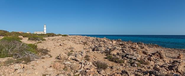 Leuchtturm am meer. panoramablick auf die spanische küste mit dem leuchtturm am felsigen strand.