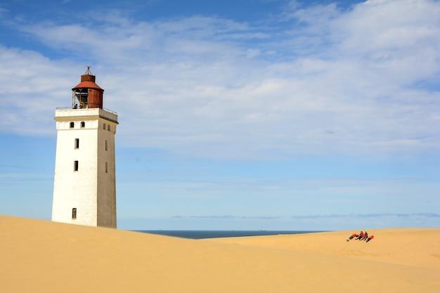 Leuchtturm am sandbedeckten strand an einem sonnigen tag