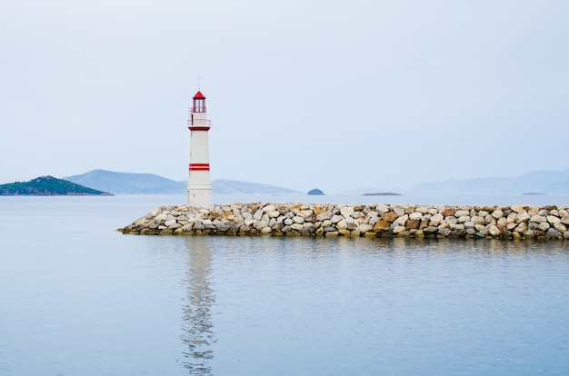 Leuchtturm auf einer steinstraße mitten im ruhigen meer mit blick auf berge und nebel.
