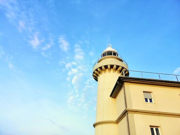 Leuchtturm, der den klaren himmel am strand in san sebastian, spanien berührt