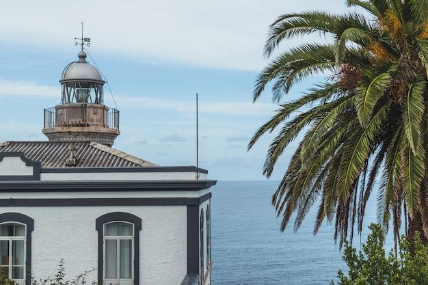 Leuchtturm in candás, asturien, spanien bei sonnenuntergang und einer palme