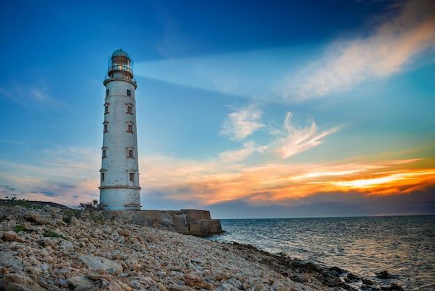 Leuchtturm suchscheinwerfer strahlen nachts durch seeluft. seestück bei sonnenuntergang