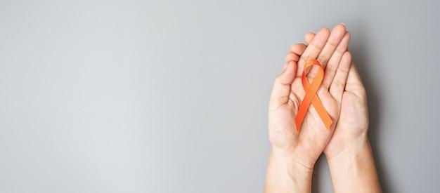Leukämie, nierenkrebstag, welt multiple sklerose, crps, selbstverletzungsmonat, orangefarbenes band zur unterstützung von menschen und krankheiten. konzept für das gesundheitswesen und den weltkrebstag