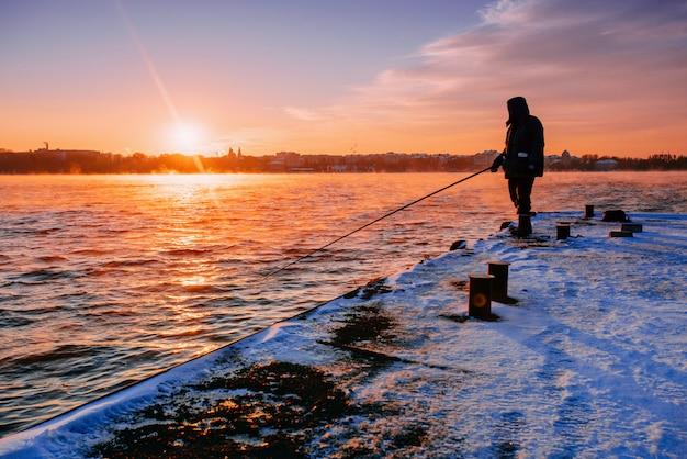 Leute am pier beobachten den sonnenuntergang