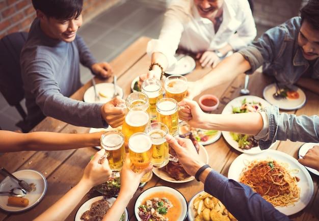 Leute auf asiaten feiern das festival, das sie gläserbier und -abendessen glücklich anstoßen