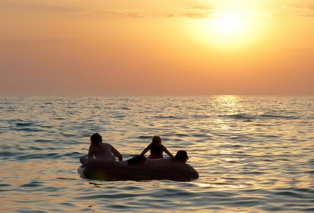 Leute auf dem floß mit dem sonnenuntergang des meeres