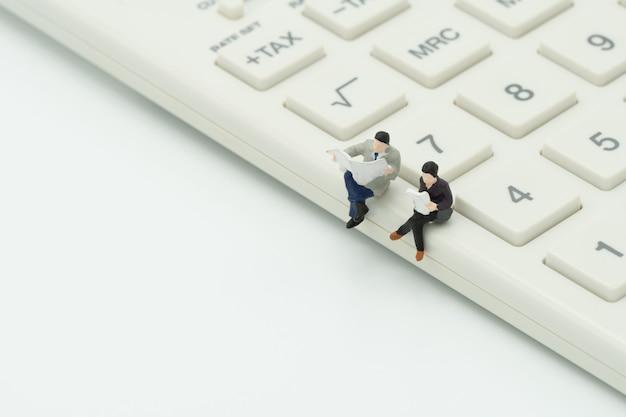 Leute der miniatur 2, die auf weißem taschenrechner sitzen