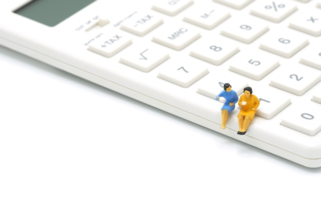 Leute der miniatur-2, die auf weißem taschenrechner sitzen