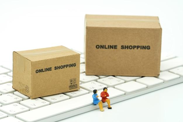 Leute der miniatur zwei, die auf weißer tastatur on-line-einkaufen sitzen
