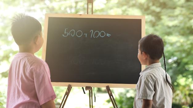 Leute des asiatischen jungen zwei, die kreativ sind, haben spaß, mathe zu lernen