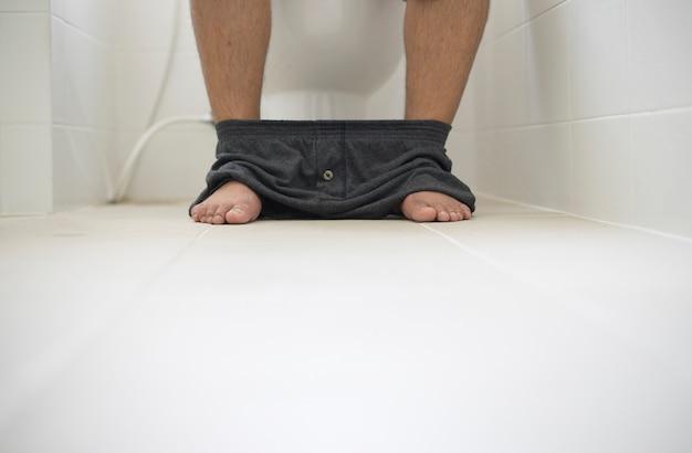 Leute des selektiven fokus, die in der toilette sitzen