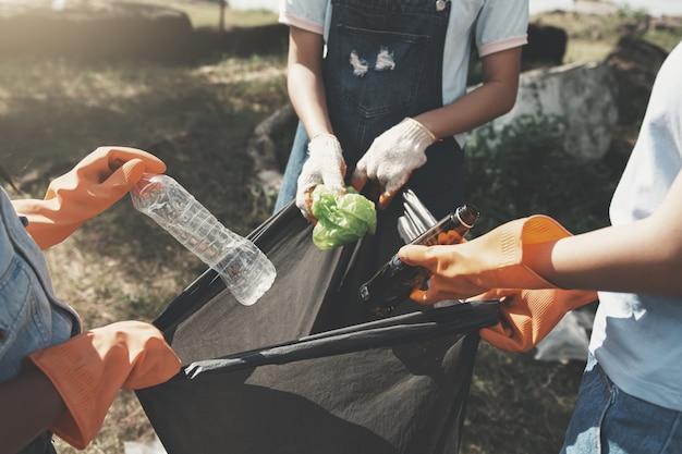 Leute, die abfall aufheben und ihn in schwarze plastiktasche für das säubern am park einsetzen