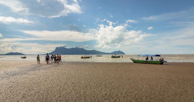 Leute, die am strand spazieren gehen, um zu den booten zu gelangen, die vom bako-nationalpark in borneo zurückkehren