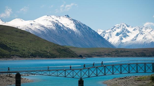 Leute, die auf der brücke über dem türkisfarbenen see mit schneebedeckten bergen gehen