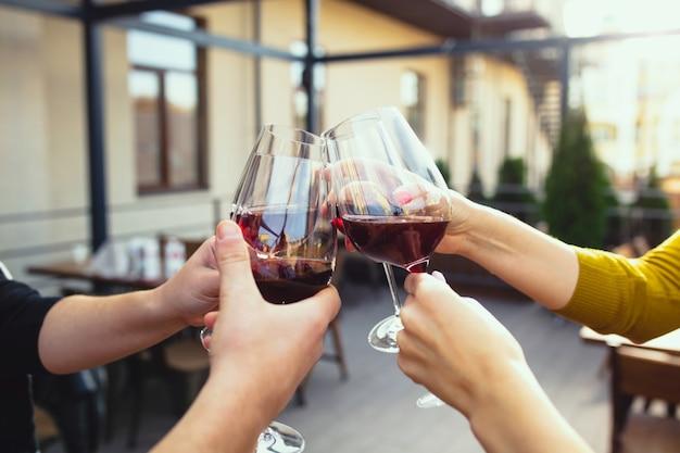 Leute, die auf der sommerterrasse des cafés oder restaurants mit wein anstoßen. fröhliche fröhliche freunde feiern sommer- oder herbstfest. schuss von menschenhand, lifestyle hautnah.