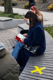 Leute, die auf distanz sitzen und maske tragen
