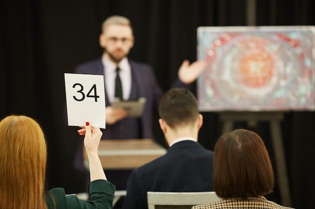 Leute, die auf einer auktion sitzen