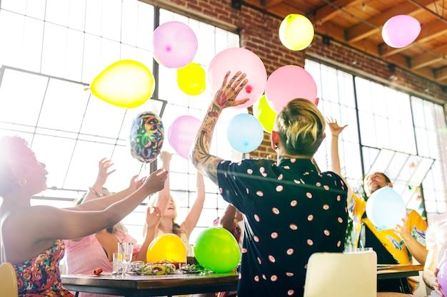 Leute, die auf einer party mit luftballons spielen