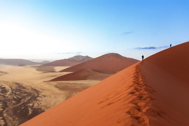 Leute, die auf schöne sonnenaufgangdünen, sossusvlei, namibia, südafrika gehen
