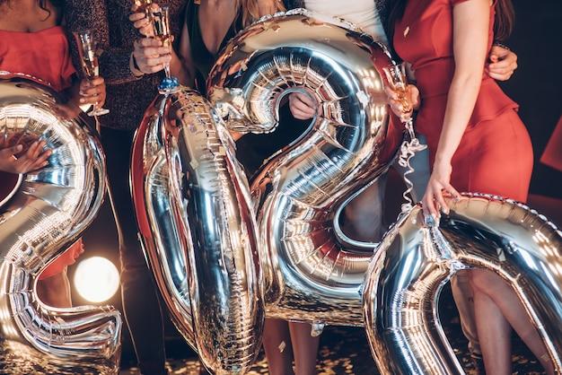 Leute, die ballons in form von zahlen des neuen jahres 2020 halten