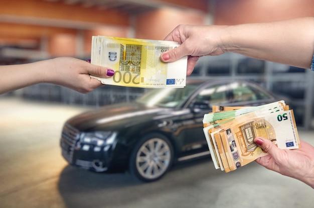 Leute, die banknoten auf einer garage halten