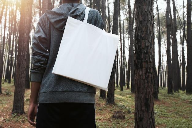 Leute, die baumwolltasche für modellfreien raum im naturhintergrund halten