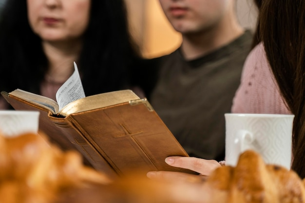 Leute, die beim abendessen aus der bibel lesen