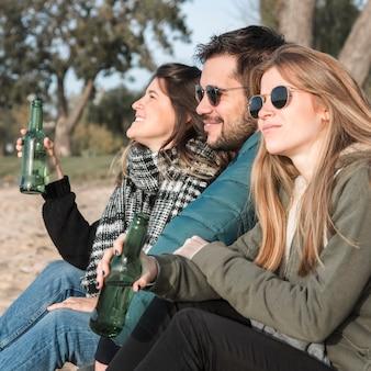 Leute, die bier auf naturhintergrund trinken