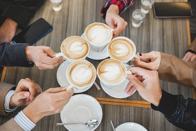 Leute, die cappuccino in der weinlese-cafeteria trinken