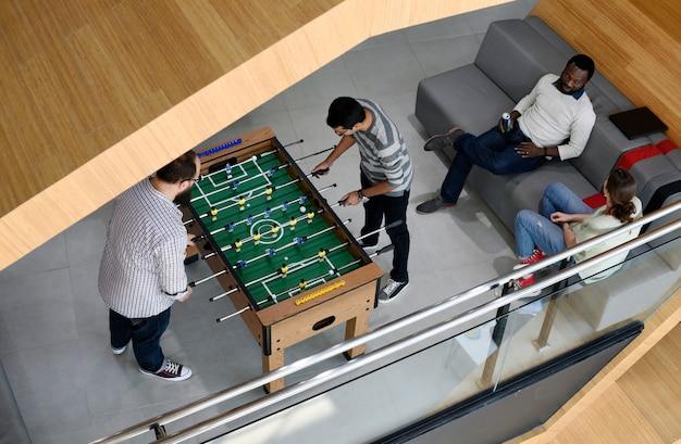 Leute, die das genießen von foosball-tabellen-fußball-spiel-erholungs-freizeit spielen