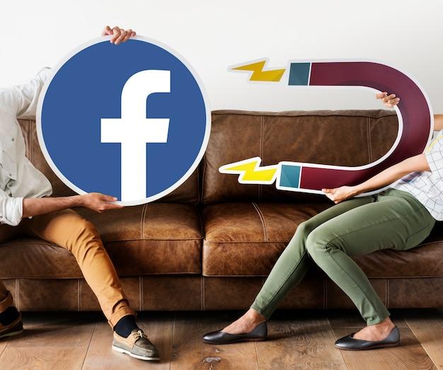 Leute, die ein facebook-symbol halten