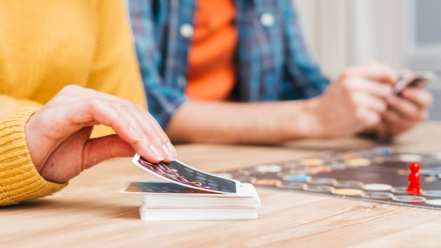 Leute, die ein geschäftsbrettspiel auf einem hölzernen schreibtisch spielen