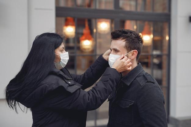 Leute, die eine schutzmaske tragen, die auf der straße steht