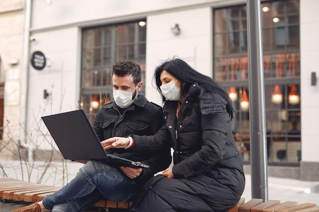 Leute, die eine schutzmaske tragen, die in einer stadt mit einem laptop sitzt