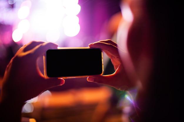Leute, die fotos mit intelligentem telefon während des live-musikkonzerts machen