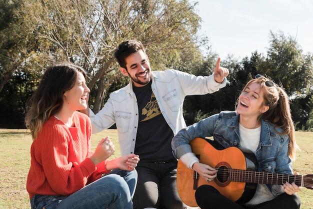 Leute, die gitarre im park spielen