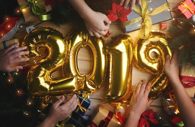 Leute, die goldenen ballon 2019 zwischen weihnachtsdekoration verzieren. draufsicht