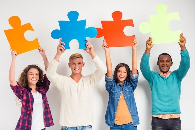 Leute, die große puzzlespielstücke halten