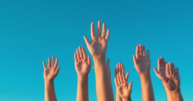 Leute, die hände auf hintergrund des blauen himmels rasen. wahl-, demokratie- oder freiwilligenkonzept