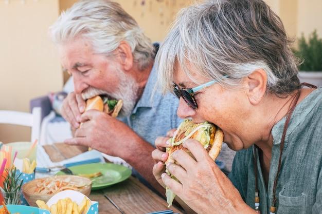 Leute, die hamburger-junkfood essen