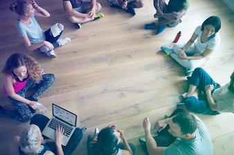Leute, die in einem Kreis in der Yogaklasse sitzen