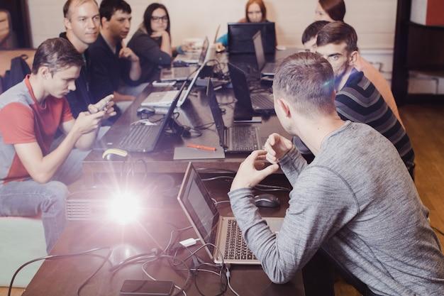 Leute, die in einem team auf sitzender tabelle des laptops arbeiten