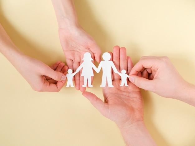 Leute, die in händen niedliche papierfamilie zusammenhalten